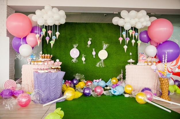 Mesa com doces e sobremesas, nuvem de balões e sorvetes Foto Premium