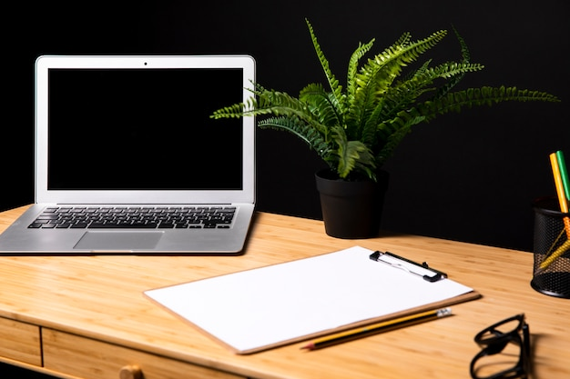 Mesa com laptop e prancheta mock-up Foto gratuita