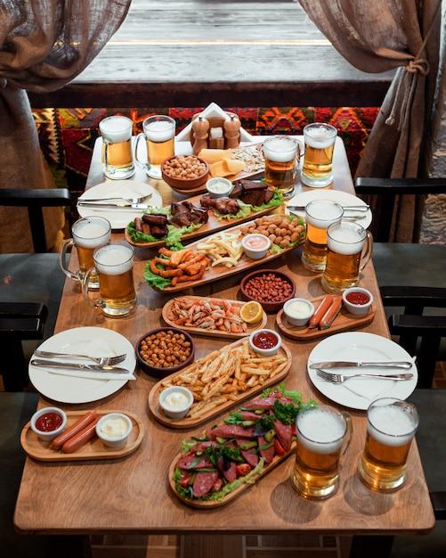Mesa com muitos petiscos e cerveja Foto gratuita