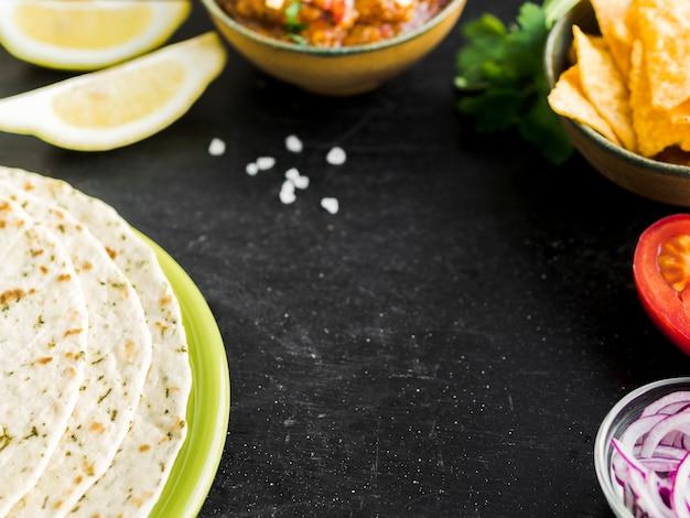 Mesa com quesadilla, nachos e legumes Foto gratuita