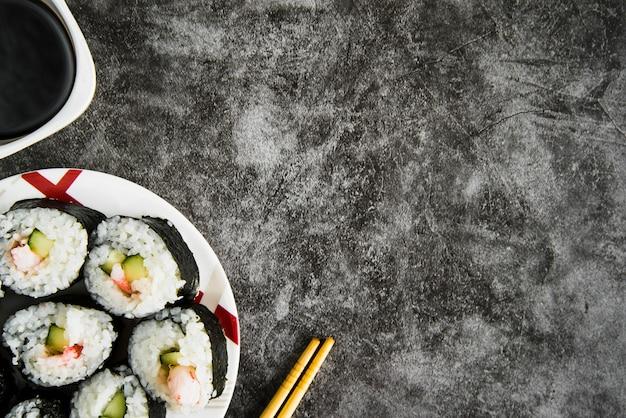 Mesa com rolos de sushi, molho de soja e pauzinhos de madeira Foto gratuita