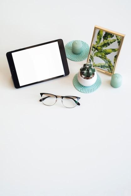 Mesa com tablet perto de moldura, planta de casa e óculos Foto gratuita