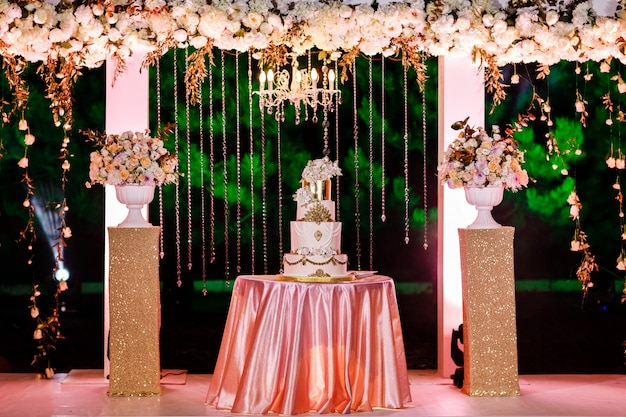 Mesa com um bolo de casamento, velas, luz e flores. Foto Premium