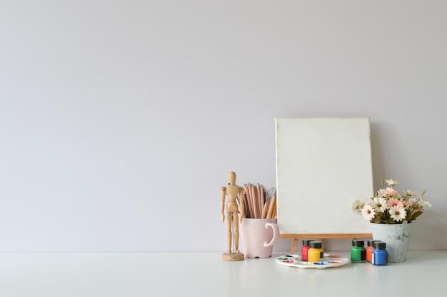 Mesa criativa de escritório com suprimentos e parede branca. Foto Premium