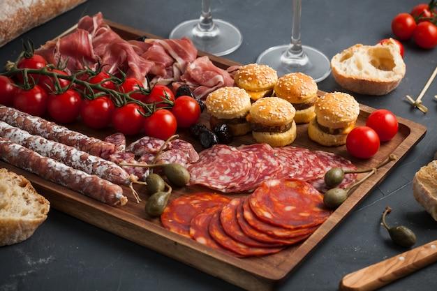 Mesa de aperitivos com diferentes antepastos, queijo, charcutaria, lanches e vinho. Foto Premium