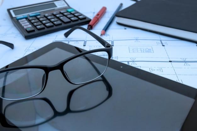Mesa de arquiteto com planos de construção, tablet, óculos no estúdio do arquiteto Foto Premium