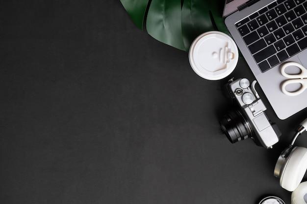 Mesa de artista computador, câmera, café e fones de ouvido na mesa preta com vista superior Foto Premium