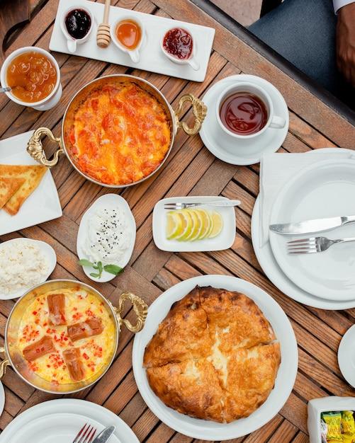 Mesa de café com variedade de alimentos e xícara de chá. Foto gratuita