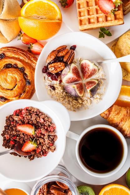 Mesa de café da manhã com aveia, waffles, croissants e frutas. Foto Premium