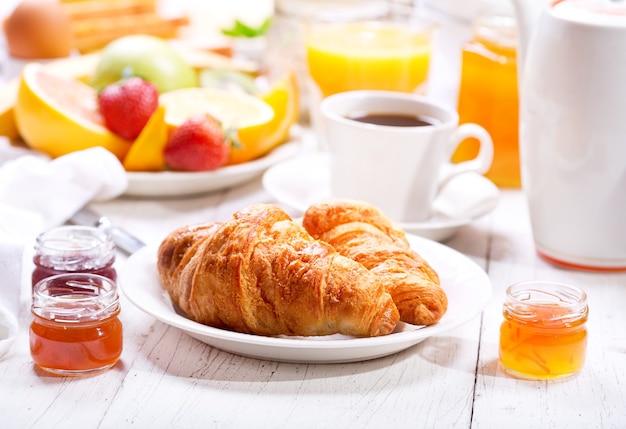Mesa de café da manhã com croissants, café, suco de laranja, torradas e frutas Foto Premium