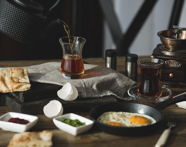 Mesa de café da manhã para duas pessoas com copos de chá e ovos fritos Foto gratuita