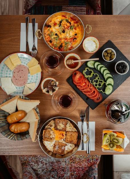 Mesa de café da manhã rica com ampla variedade de alimentos, incluindo ovos, salsichas, queijo creme Foto gratuita