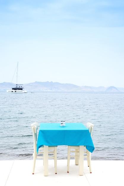 Mesa de café servida com uma toalha de mesa azul perto da costa do mar para umas férias relaxantes Foto Premium