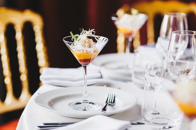 Mesa de casamento decorada com pratos brancos, copos de vinho e coquetel no espaçoso salão Foto Premium