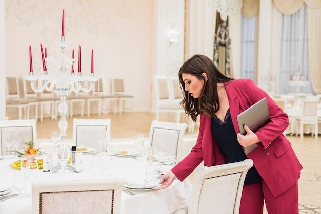 Mesa de configuração de gerente de banquete feminino para evento Foto gratuita