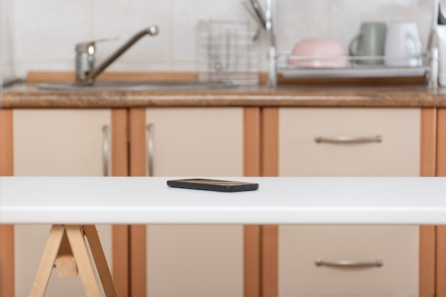 Mesa de cozinha e celular no fundo da cozinha. smartphone esquecido Foto Premium