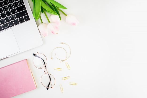 Mesa de escritório. a forma das mulheres com portátil, ramalhete cor-de-rosa, vidros do olho do caderno e acessórios em um fundo branco. Foto Premium