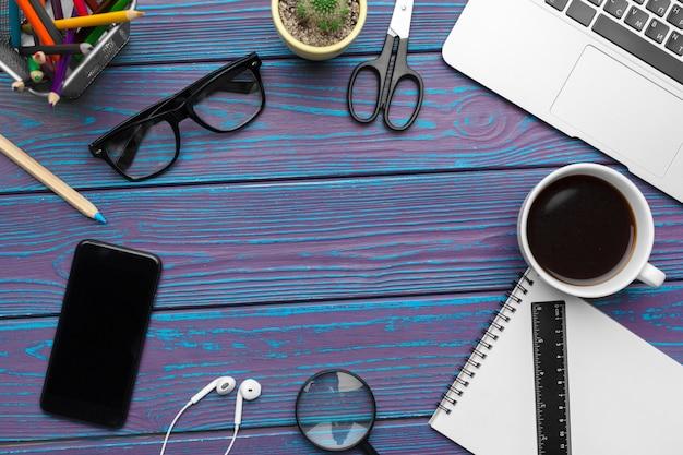 Mesa de escritório com bloco de notas em branco, laptop e material de escritório vista superior Foto Premium