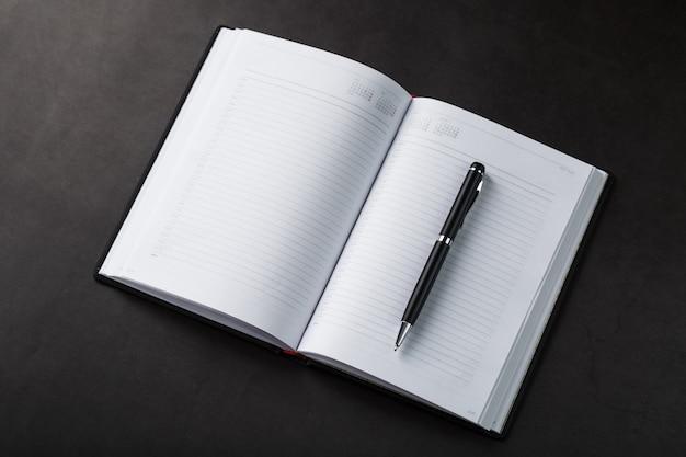 Mesa de escritório com bloco de notas preto e caneta sobre fundo preto. vista superior com espaço de cópia. conceito de metas e objetivos de negócios Foto Premium