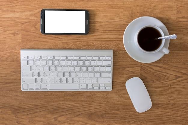 Mesa de escritório com computador de teclado e xícara de café e mouse de computador e smartphone Foto Premium