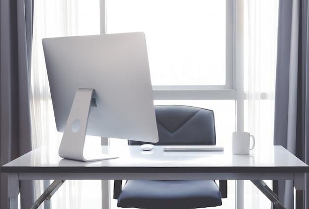 Mesa de escritório com computador desktop, xícara de café e equipamento de escritório Foto Premium