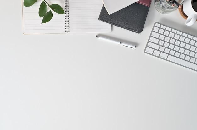 Mesa de escritório com computador do teclado do espaço da cópia da vista superior, café, papel do caderno e material de escritório na mesa de escritório. Foto Premium
