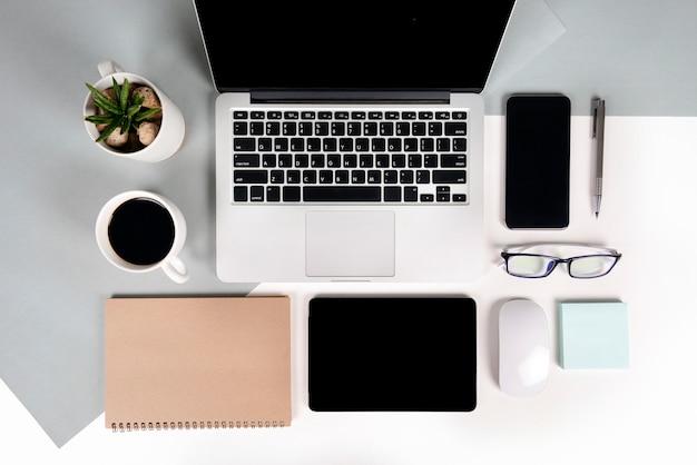 Mesa de escritório com computador portátil, notebook, tablet digital e celular em dois tons b Foto Premium
