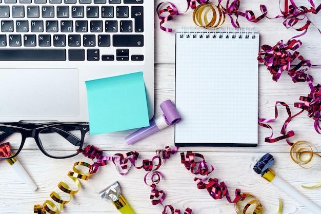 Mesa de escritório com laptop e bloco de notas aberto decorado com flâmulas de festa. conceito de resoluções de ano novo Foto Premium