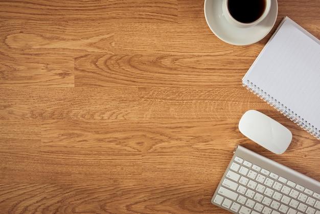 Mesa de escritório com o bloco de notas, computador e xícara de café e mouse de computador Foto Premium