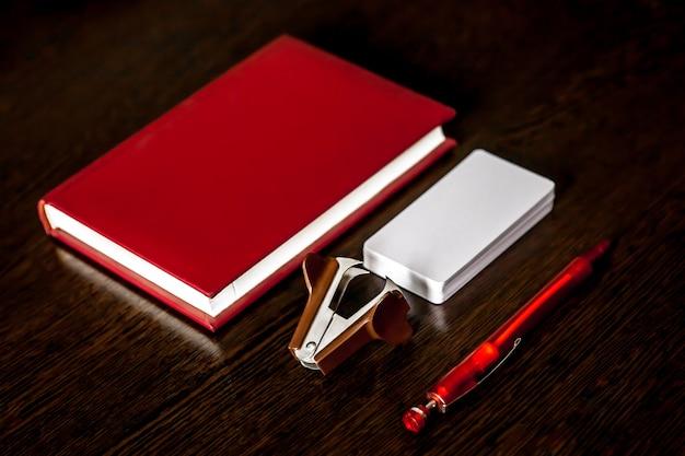 Mesa de escritório com o bloco de notas, lápis coloridos, suprimentos e cartões de visita. Foto Premium
