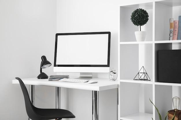 Mesa de escritório com tela de computador e cadeira Foto gratuita