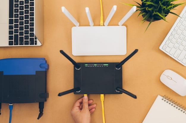 Mesa de escritório plana leigos com roteador wifi, computador e suprimentos vista superior Foto Premium