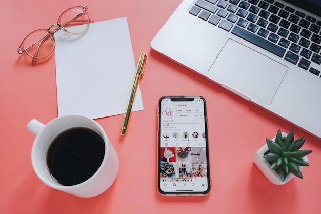 Mesa de espaço de trabalho plana leigos e telefone móvel com uma aplicação na tela com fundo de laptop e café. Foto Premium