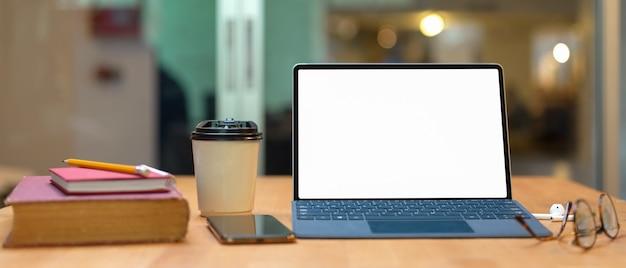 Mesa de estudo com livros, mock-se tablet com teclado, smartphone, óculos e copo de papel Foto Premium