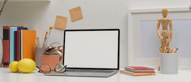 Mesa de estudo moderna com laptop mock-up, óculos, ferramentas de pintura, suprimentos e decorações Foto Premium