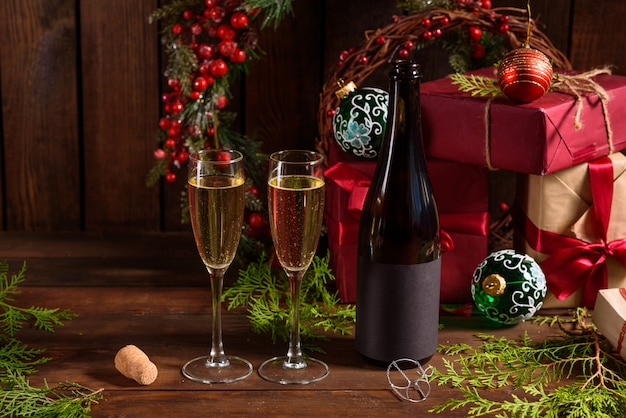 Mesa de férias de natal com copos e uma garrafa de vinho de champanhe Foto Premium