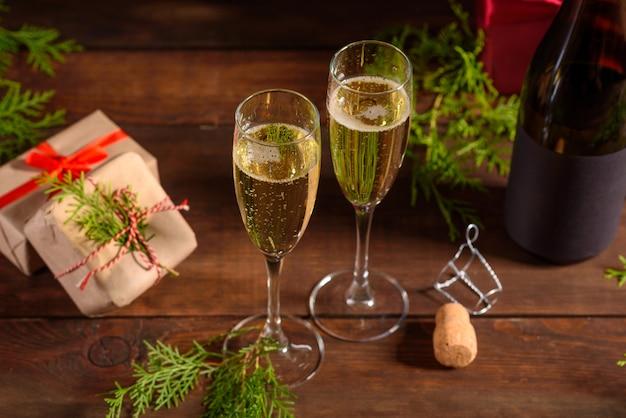 Mesa de férias de natal com copos e uma garrafa de vinho Foto Premium