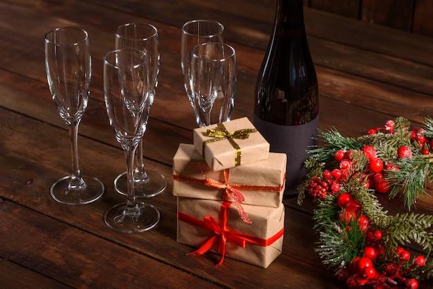 Mesa de férias de natal com copos e uma garrafa e presentes Foto Premium