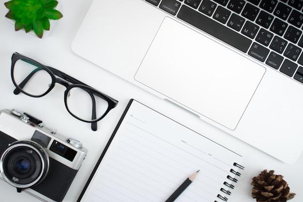 Mesa de fotógrafo com câmera, laptop e óculos prontos para trabalhar em uma mesa branca, vista superior Foto Premium