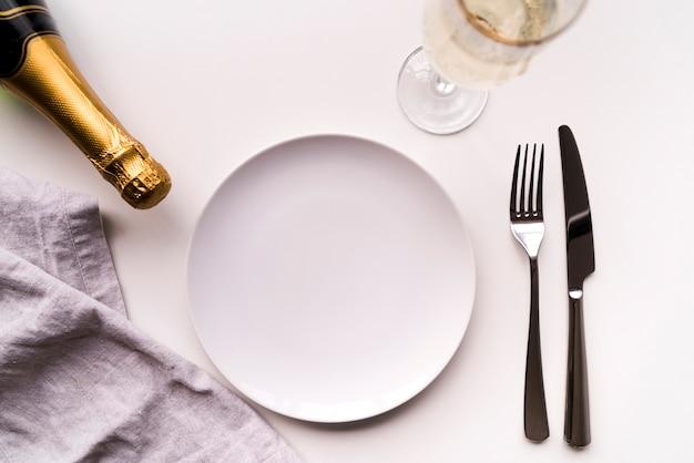 Mesa de jantar com prato vazio e garrafa de champanhe sobre fundo branco Foto gratuita