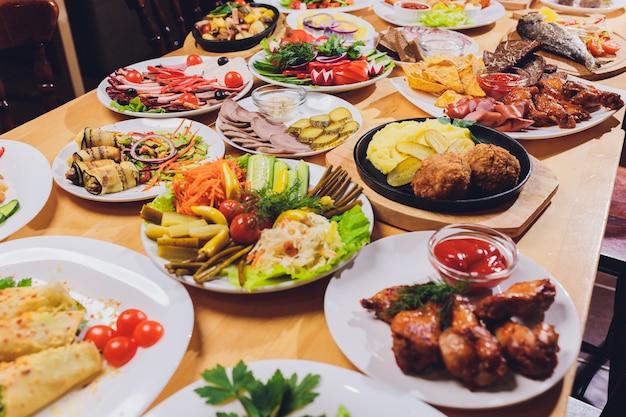 Mesa de jantar com uma variedade de lanches e saladas. salmão, azeitonas, vinho, legumes, torradas de peixe grelhado. Foto Premium