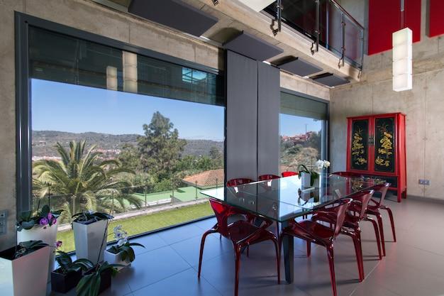 Mesa de jantar de vidro com cadeiras de metacrilato vermelho, interior da casa moderna com orquídeas. casa de concreto de altura dupla. com vista para o campo Foto Premium