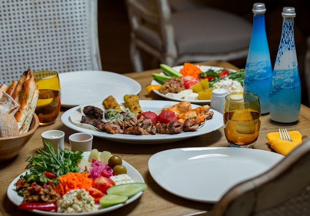 Mesa de jantar doada com variedade de alimentos e duas garrafas azuis de água mineral. Foto gratuita