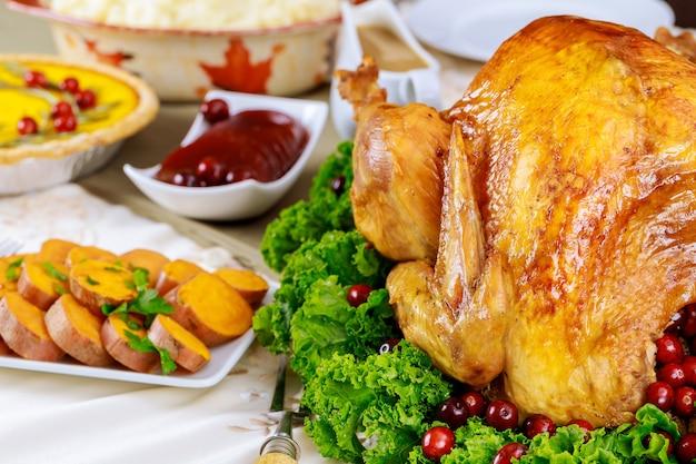 Mesa de jantar festiva servida com peru, decorada com couve e cranberry. Foto Premium