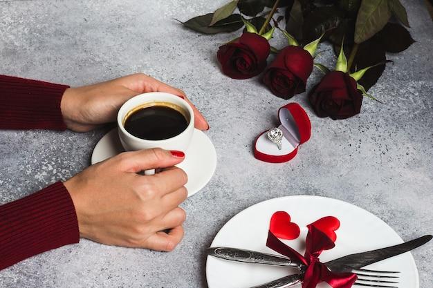 Mesa de jantar romântico dia dos namorados configuração mão de mulher segurando a xícara de café Foto gratuita