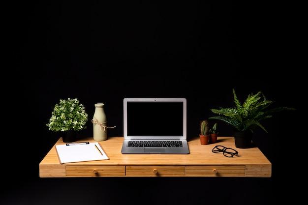 Mesa de madeira arrumada com laptop cinza Foto gratuita
