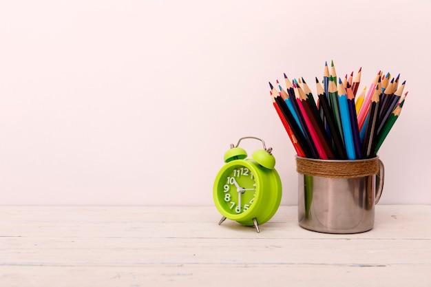Mesa de madeira branca com despertador e lápis coloridos em branco Foto Premium
