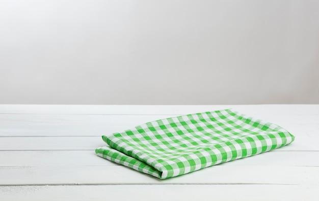 Mesa de madeira branca com toalha de mesa verde para montagem do produto Foto Premium