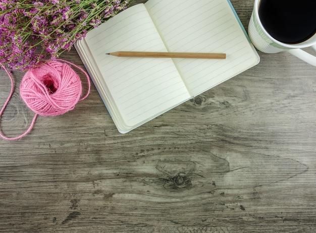 Mesa de madeira cinza plana leigos, vista superior com artigos de papelaria, incluindo caderno e lápis com uma xícara de café Foto Premium