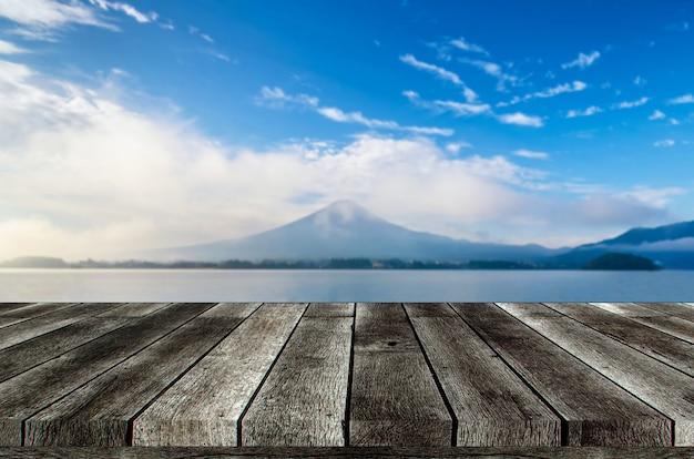 Mesa de madeira cinza vazia ou terraço de madeira com bela vista da montanha fuji com céu azul no início da manhã Foto Premium